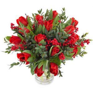 Julbukett med röda jultulpaner, röda bär och gröna blad. Skicka blommorna med ett blomsterbud från Euroflorist!