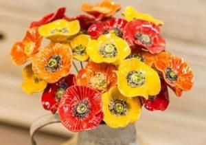 Handgjorda keramikblommor, här vallmor i gult, orange och rött. Säljes styckvis hos Keramik Blomma i Åkarp.